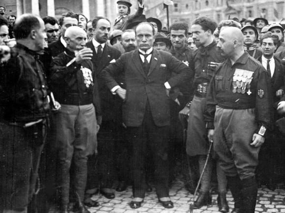Žygis į Romą. Pirmame plane B. Musolinis. Dešiniausias - maršalas de Bono. Fašistų vadai ir jų bendraminčiai žengia pasidabinę apdovanojimais, apsivilkę fašistų uniformą - juodus marškinius ir apsiavę aulinius batus