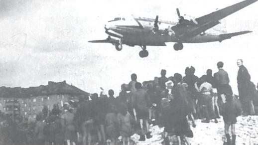 Mokiniai stebi amerikiečių transporto lėktuvo skrydi i Berlyną. 1948 m. Sovietų Sąjungos pastangomis buvo užblokuotas Vakarų Berlyno aprūpinimas. Tik Vakarų pagalba privertė nutraukti blokadą. Oro tiltu buvo pergabenta 1,7 mln. tonų krovinių, atlikta 280 tūkst. skrydžių
